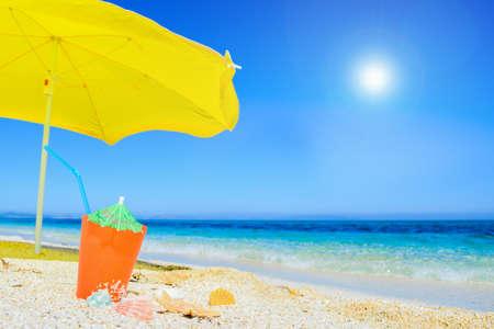 beach umbrella and cocktail under a bright sun Stock Photo