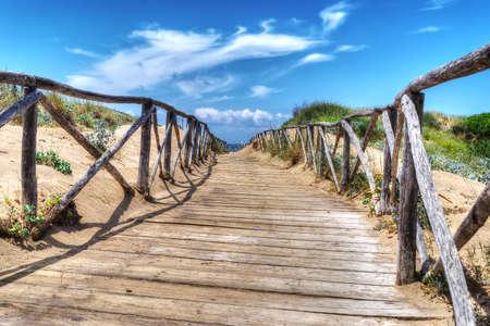 hand rail: wooden boardwalk heading to the beach. Shot in Sardinia, Italy