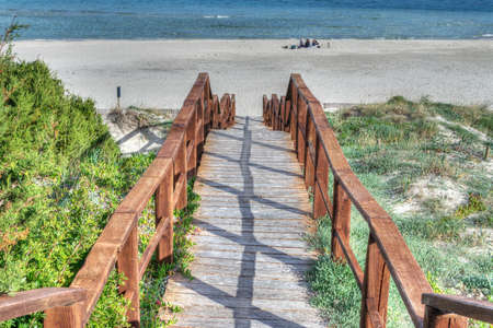 hand rail: wooden stairs to the beach in hdr