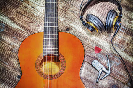riff: classic guitar and headphones on a wooden background Stock Photo