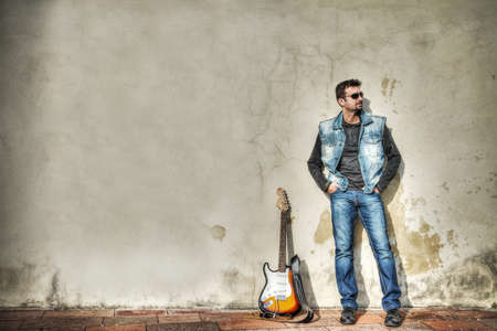 man and guitar against a grungy wall. Processed for hdr tone mapping effect photo