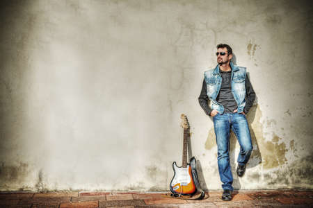 man and guitar against a grungy wall. Processed for hdr tone mapping effect