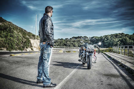 biker standing next to a classic motorcycle in hdr tone mapping effect Stock Photo
