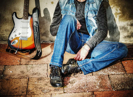man and electric guitar leaning against a grunge wall photo
