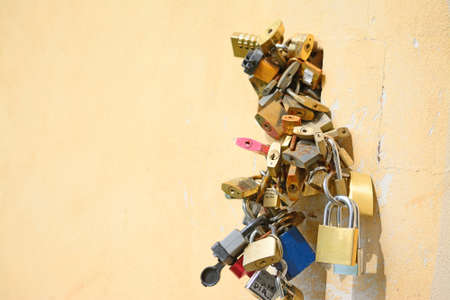 padlocks: cluster of padlocks on a yellow wall