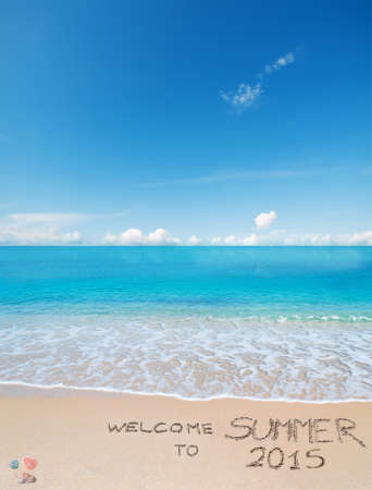 welcome to summer 2015 written on a tropical beach under clouds Stock Photo