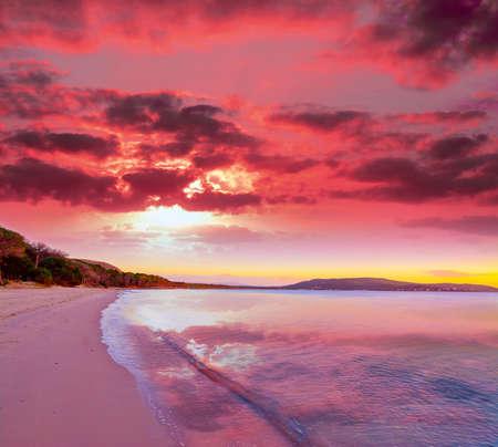 růžový západ slunce v Mugoni pláži, Sardinii