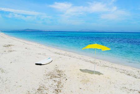 surfplank en parasol op het zand