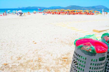 botes de basura: botes de basura de metal en la arena en el verano