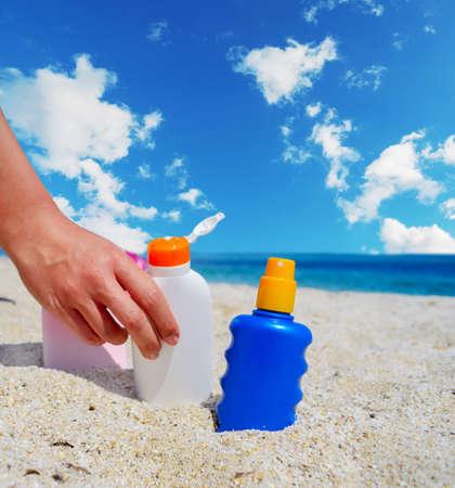lotion bottle: girl holding a suntan lotion bottle