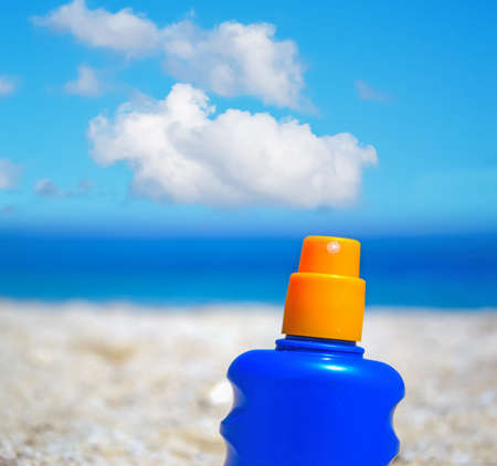 suntan lotion bottle in the sand Standard-Bild