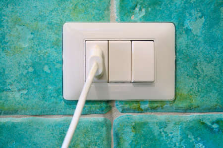wall socket: white plug in a wall socket with turquoise majolica Stock Photo
