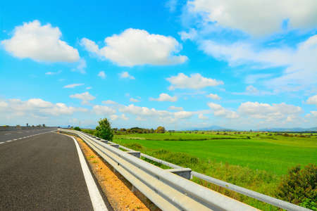 guard rail: guard rail in a country road under clouds Stock Photo