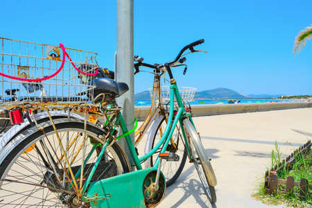 beach cruiser: old bikes by the sea in Alghero, Italy