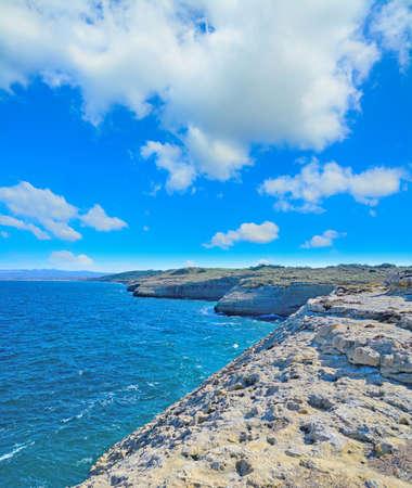 skim: rocky shore in Porto Torres under huge clouds, Sardinia