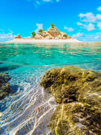 under surface: over and under water surface of a tropical atoll on a clear day Stock Photo