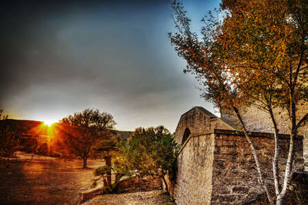 end of a long day: brick wall and trees in the countryside at dusk, Sardinia