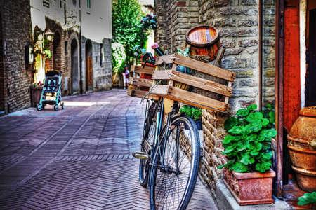 wicker: bicicleta vieja con el caso de madera contra una pared de ladrillos en San Gimignano, Italia Foto de archivo
