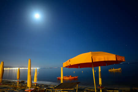 moon chair: parasols by the sea under a bright moon, Sardinia Stock Photo