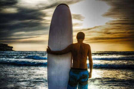 surfer and surfboard on the beach at sunset