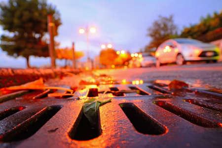 dark city: close up of a drainage sewer at sunset Stock Photo