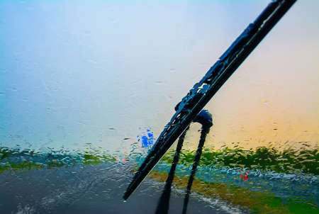 rain water: wiper on a wet windshield at sunset