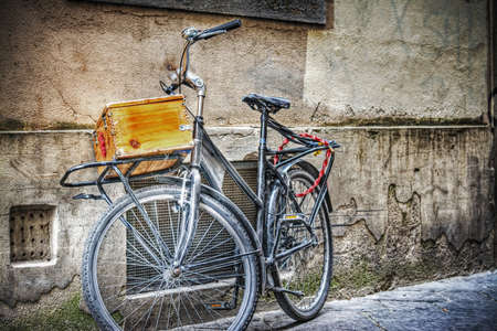 old bike with wooden case against a wall in florence, Italy