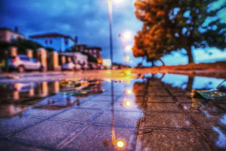 dark city: close up of a wet sidewalk by night