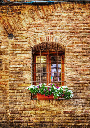 window sill: rustic window with metal grill in a brick wall in San Gimignano, Italy Stock Photo