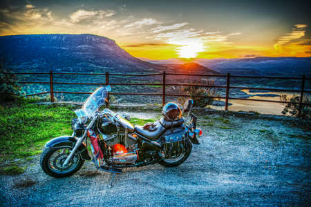 handlebars: classic motorcycle on the edge of the road at sunset Stock Photo