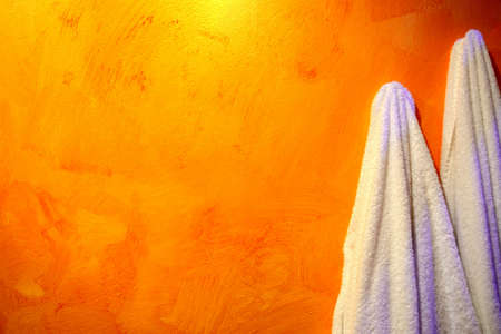 white towels hanging on an orange wall Stock Photo