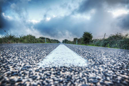 highway: empty country road under a grey sky seen from the ground