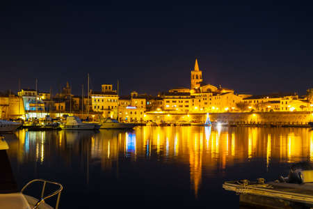 Alghero cityscape under a clear sky at night, Italy