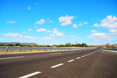guardrail: country road under a blue sky with soft clouds