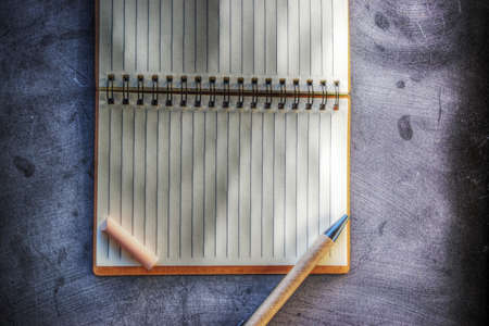 chalks: notebook, pen and chalks on a blackboard Stock Photo