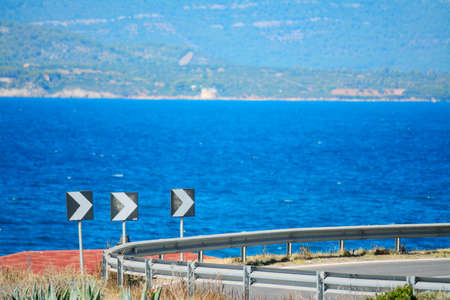 risks ahead: curve road signs by the sea in Alghero, Italy
