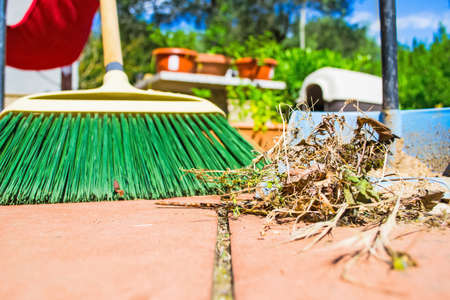garden waste: close up of grass and broom on a red floor