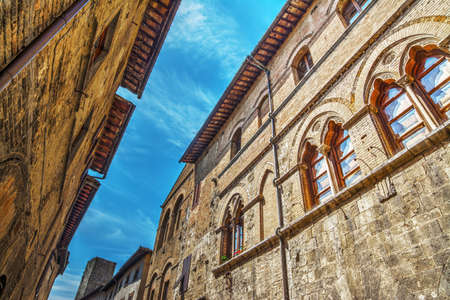 the silence of the world: narrow street in San Gimignano on a clear day, Italy Stock Photo