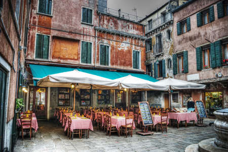 restaurant tables and chiairs in a small square in Venice, Italy Standard-Bild