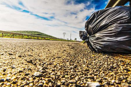 black plastic garbage bag: trash bag on the ege of a country road