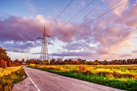 torres el�ctricas: torres de alta tensi�n por un camino rural al atardecer