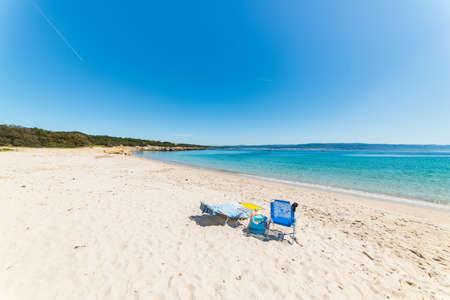 idling: beach chairs on a empty beach under a clear sky