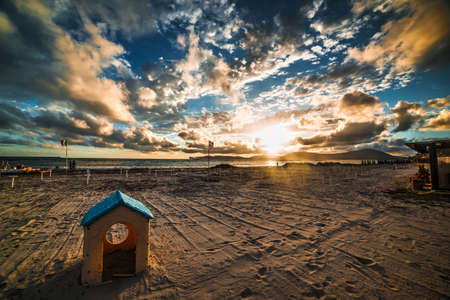 plastic toy house on the beach at sunset