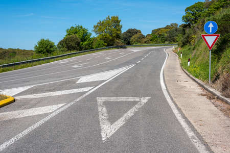 ordenanza: give way sign on asphalt on a country road