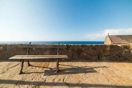 skim: old wooden bench by Castelsardo coastline, Sardinia