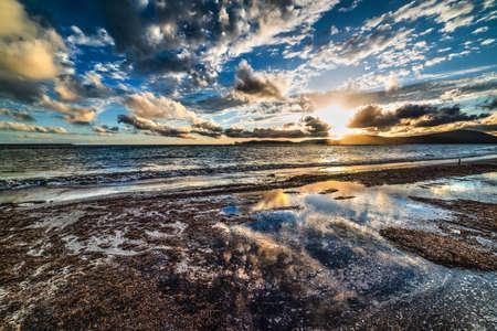 seaweeds: cloudy sky over the shore at sunset, Sardinia