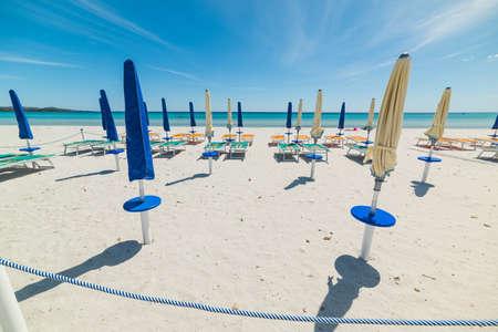 closed parasol in La Cinta beach, Sardinia Stock Photo