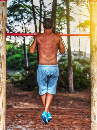 grapple: man doing pull ups in a park at sunset Stock Photo