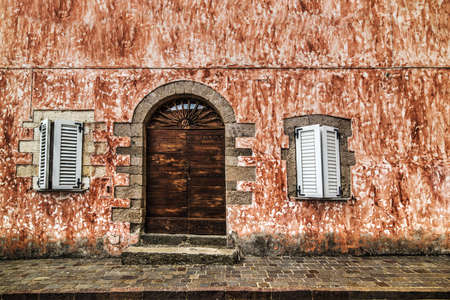 wooden door in a rustic wall in Sardinia, Italy Stock Photo