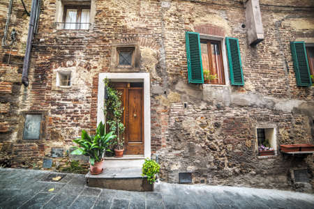 montepulciano: wooden door in a rustic wall in Montepulciano, Tuscany